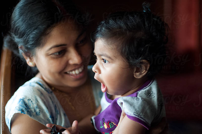 Toddler sharing a cheerful moment with her mother by Saptak Ganguly for Stocksy United