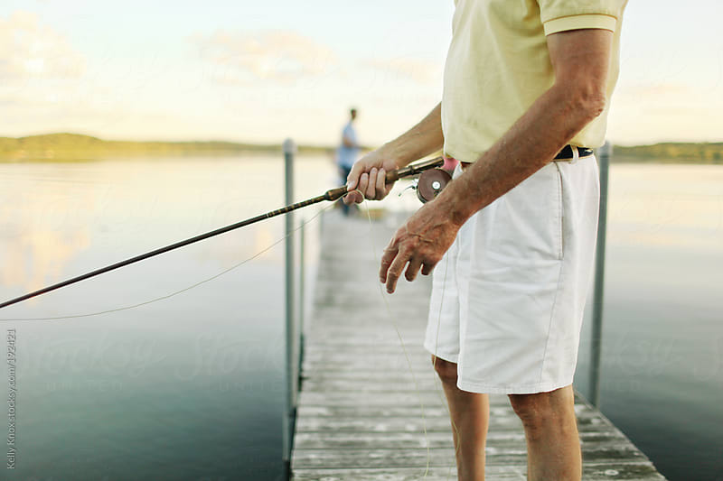 man fly fishing in a lake by Kelly Knox for Stocksy United