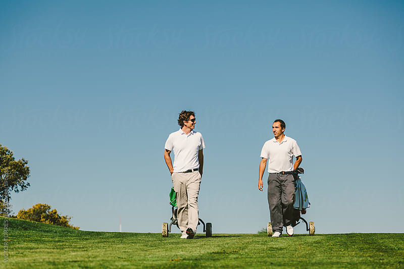 Two Men Walking Through a Golf Course by VICTOR TORRES for Stocksy United