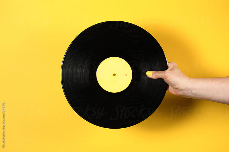 Hand holding vinyl record over yellow background by Pixel Stories for Stocksy United