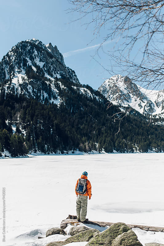 Back view of a mountaineer on the snowy landscape. by Jordi Rulló for Stocksy United