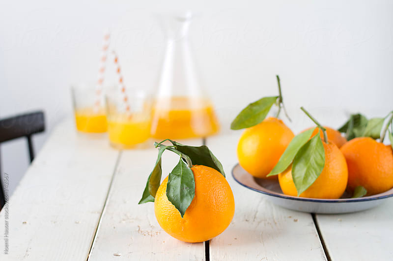 Oranges with leaves  by Noemi Hauser for Stocksy United