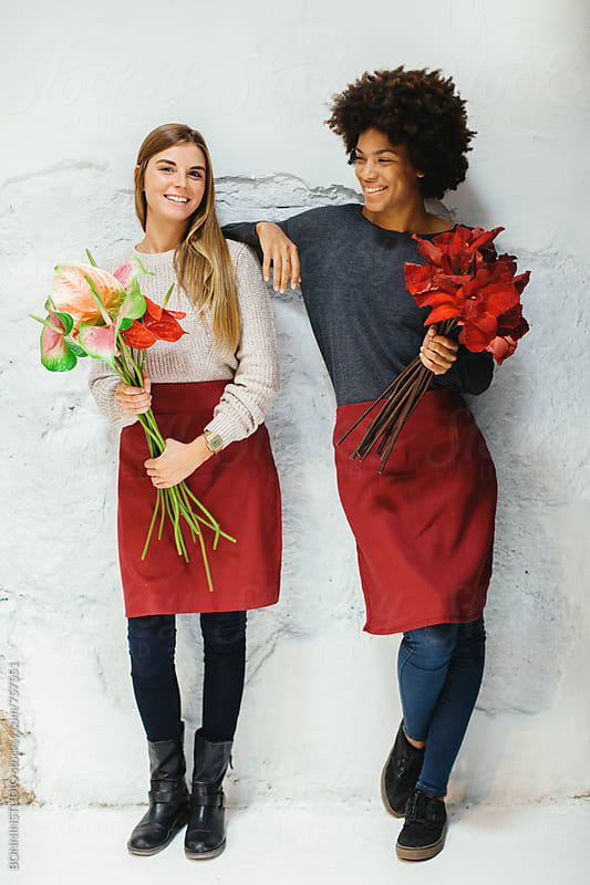 Women holding a bouquet of flowers standing on a white wall. by BONNINSTUDIO for Stocksy United