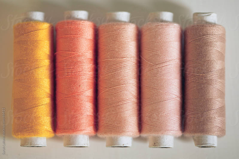 Orange and peach thread spools lined up on a table. by Sarah Lalone for Stocksy United