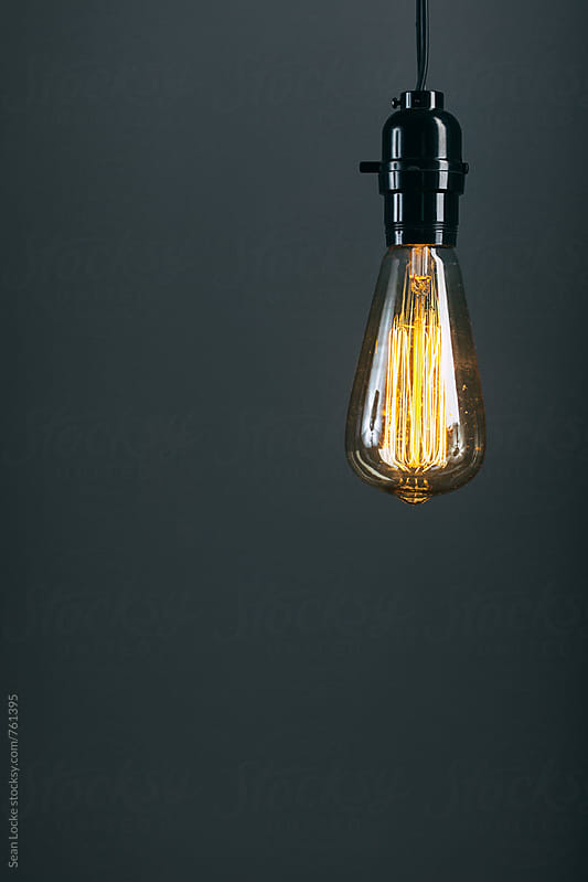 Light: Antique Bulb Hangs In Front Of Blank Wall by Sean Locke for Stocksy United