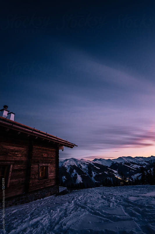 alpine cabin in winter landscape at sunset by Leander Nardin for Stocksy United