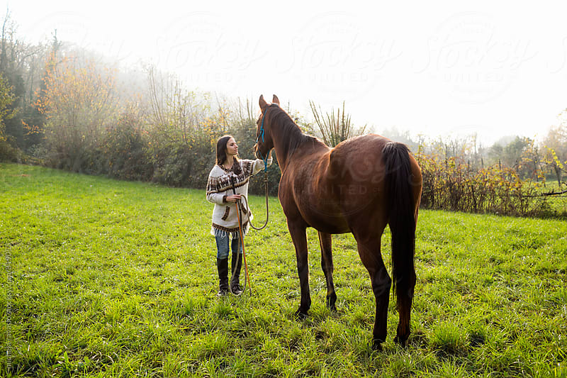 Woman caressing her horse by michela ravasio for Stocksy United