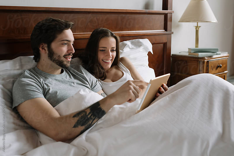 Couple using tablet in bed by Alberto Bogo for Stocksy United
