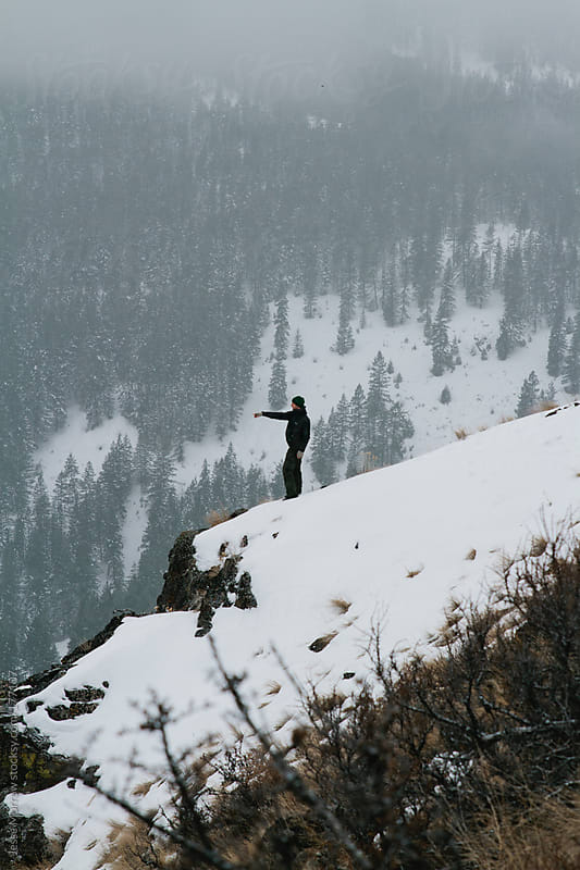 Young man stands on edge of mountain by Jesse Morrow for Stocksy United