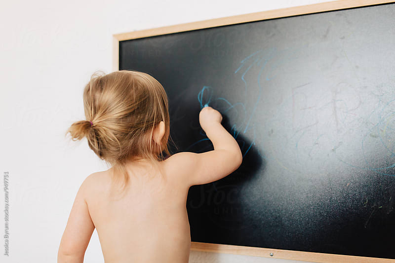Toddler girl drawing with blue chalk on chalkboard in living room. by Jessica Byrum for Stocksy United