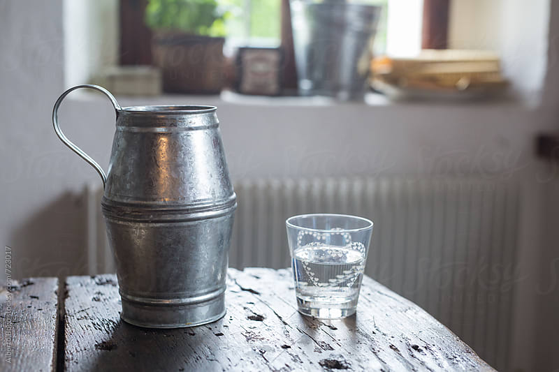 An aluminium pitcher and a glass of water on wooden table by Alberto Bogo for Stocksy United
