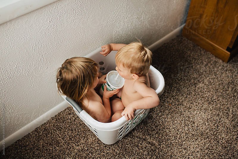 Blonde toddler siblings sneaking a drink of soda while sitting in a white laundry basket. by Jessica Byrum for Stocksy United