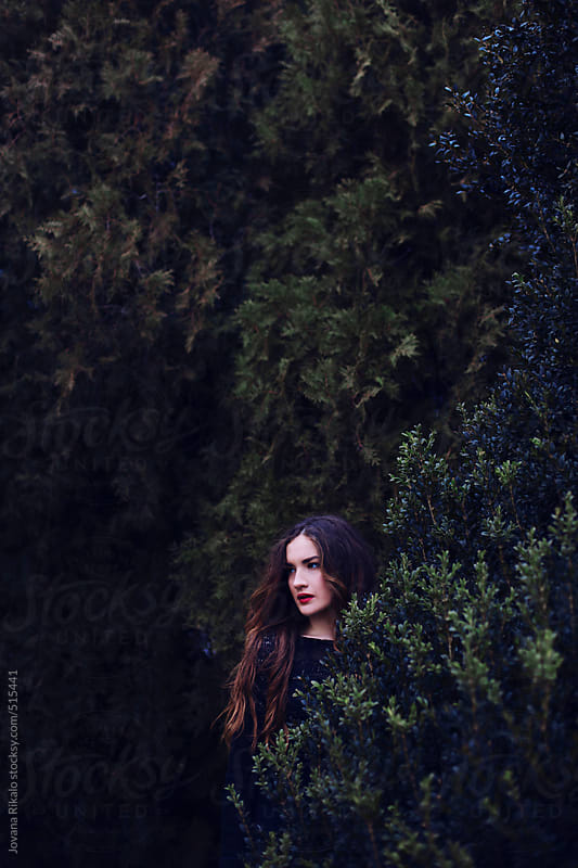 Beautiful young woman standing against tree at park by Jovana Rikalo for Stocksy United