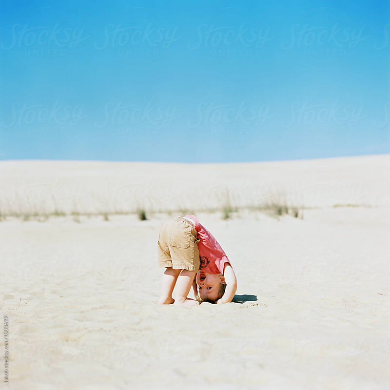 Cute young boy trying to stand on his head on a sand dune by Jakob for Stocksy United