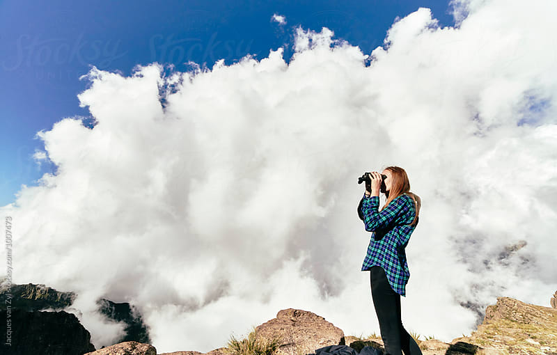 Female hiker with binoculars moments before getting covered by a big cloud. by Jacques van Zyl for Stocksy United