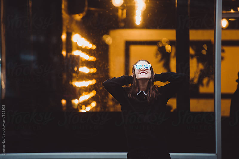 Happy woman standing outside bar in the street by Lauren Naefe for Stocksy United