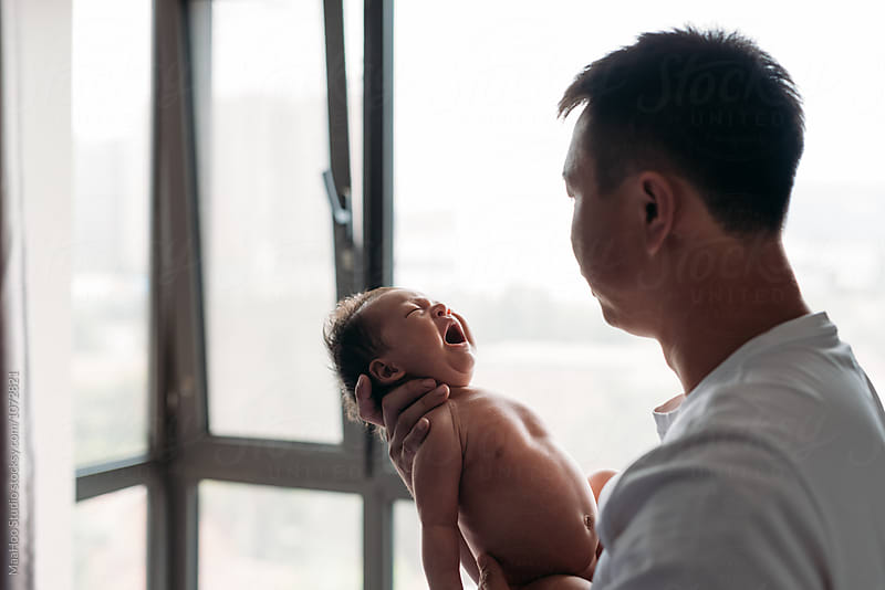 Father staring at his newborn baby by MaaHoo Studio for Stocksy United