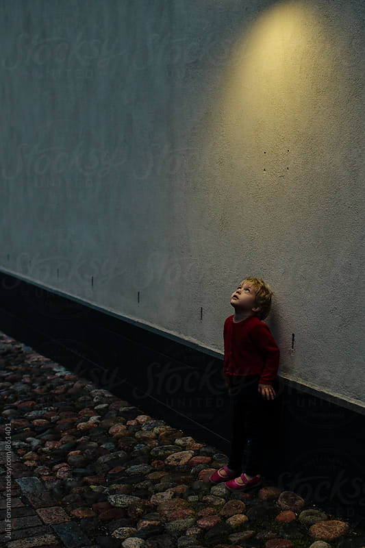 Small child looking up into the light of a street light at dusk. by Julia Forsman for Stocksy United