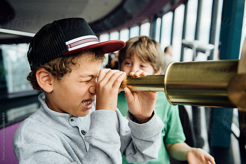 Side view of boy looking through gold telescope by Trent Lanz for Stocksy United
