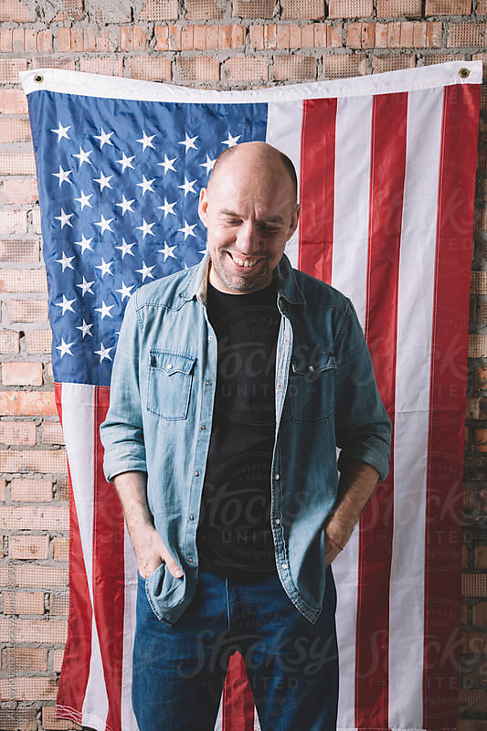 real happy man standing against an american flag by Alexey Kuzma for Stocksy United