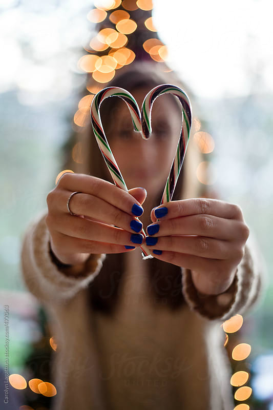 Teenage girl holding a candy cane in the shape of a heart in front of the Christmas tree by Carolyn Lagattuta for Stocksy United