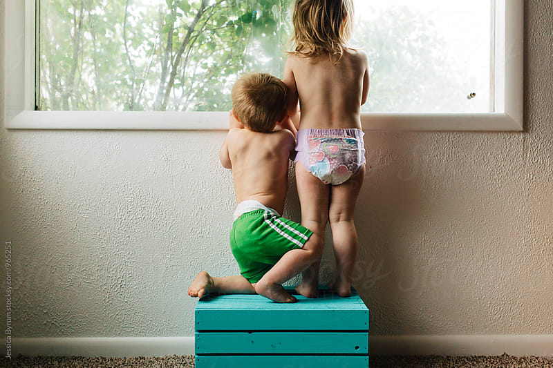 Toddler siblings on blue crate by Jessica Byrum for Stocksy United