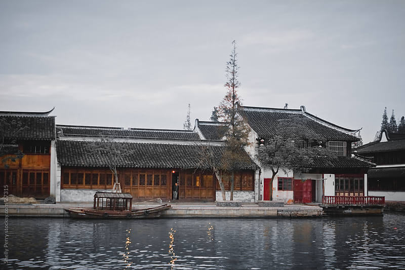 Water Taxi parked in front of buildings in a traditional water village outside of Shanghai, China by Shelly Perry for Stocksy United