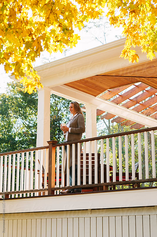 Woman on Porch Enjoying Morning Coffee in Autumn by Raymond Forbes LLC for Stocksy United