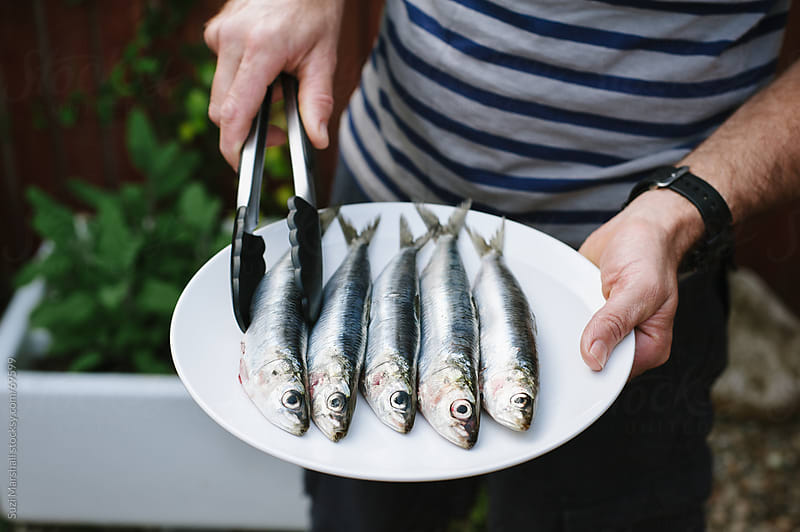 Man holding a plate of sardines  by Suzi Marshall for Stocksy United