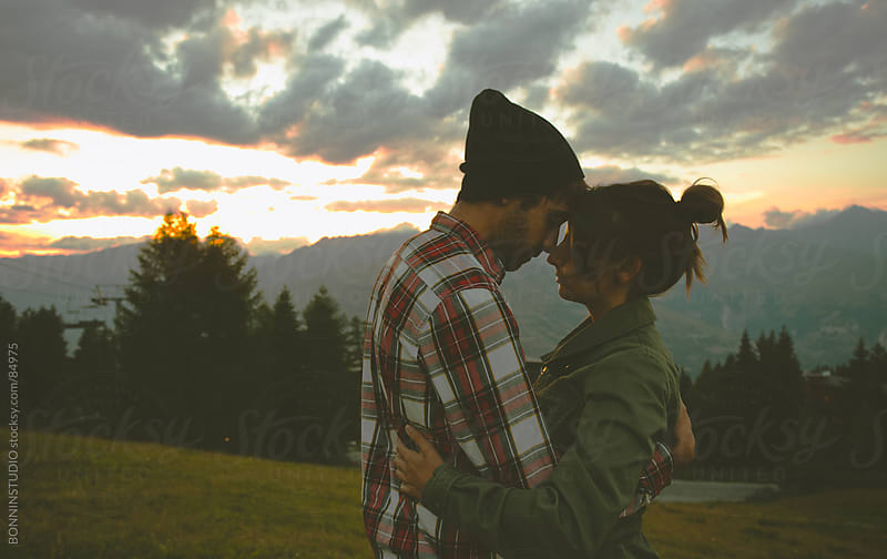 Lovely cute couple in beautiful sunset landscape. by BONNINSTUDIO for Stocksy United