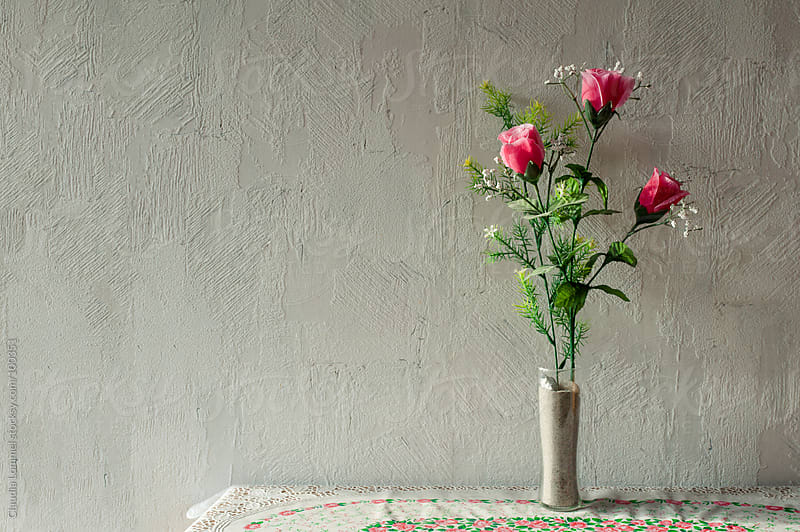 Odd Plastic Flower Decoration in Front of  Roughcast Wall by Claudia Lommel for Stocksy United