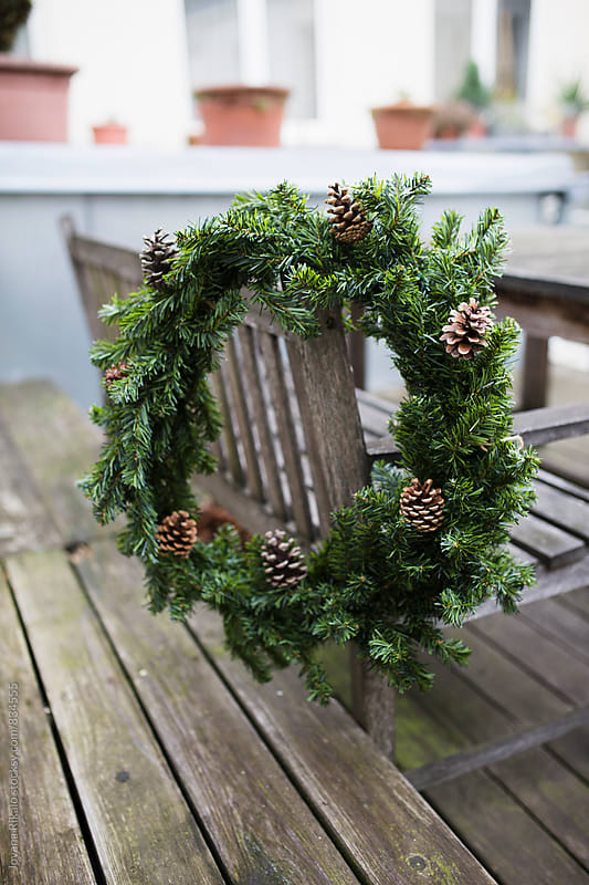 Christmas wreath hanging on a bench by Jovana Rikalo for Stocksy United