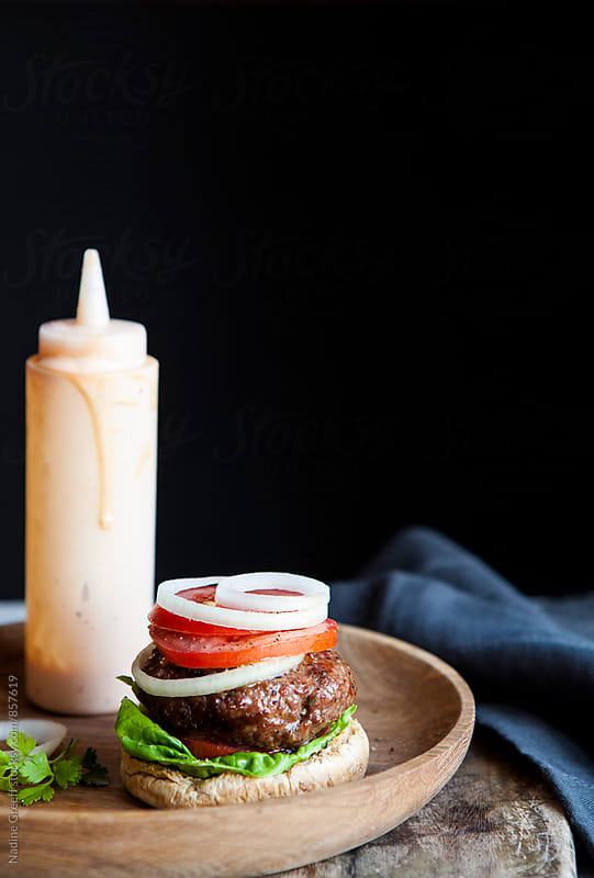 Hamburger with tomato and onion and bottle of sauce by Nadine Greeff for Stocksy United