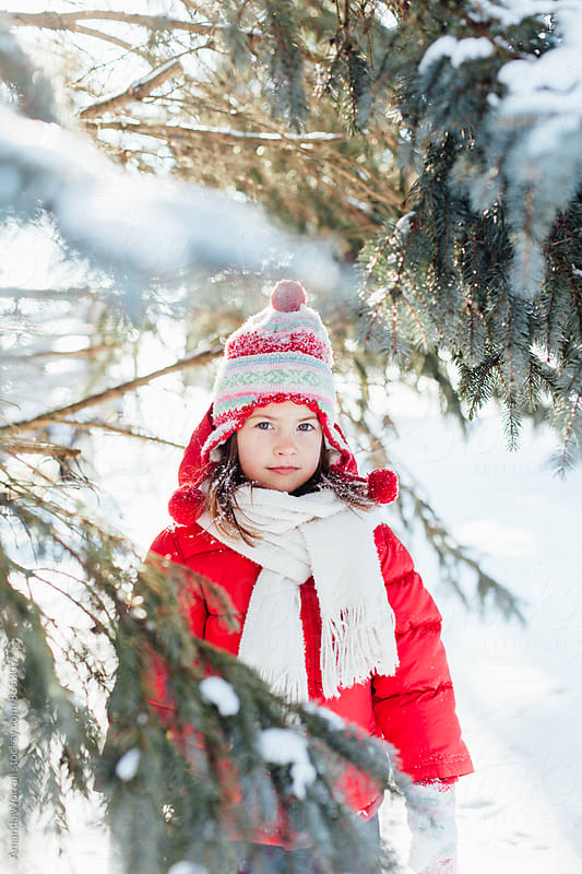 Beautiful young girl wearing bright winter clothes looks at camera sweetly by Amanda Worrall for Stocksy United