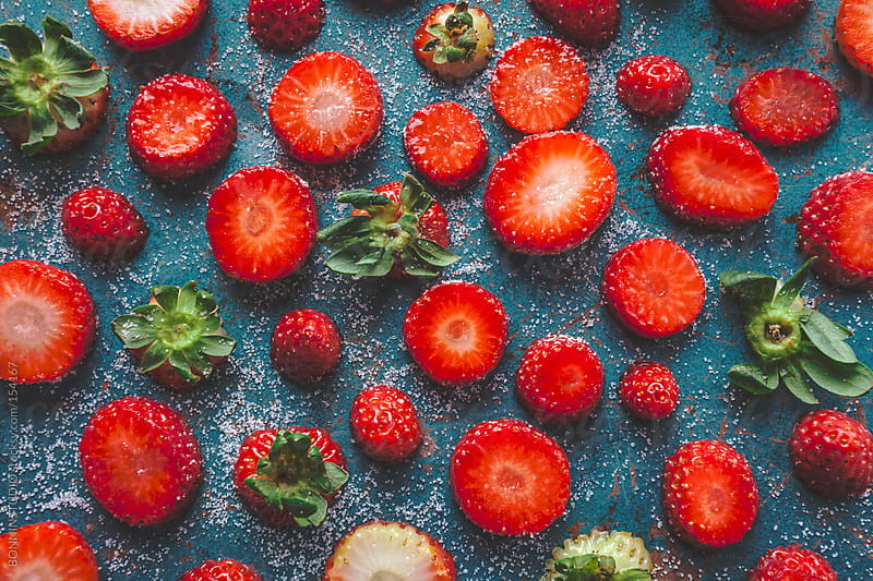 Overhead of composed strawberries pieces on blue background. by BONNINSTUDIO for Stocksy United