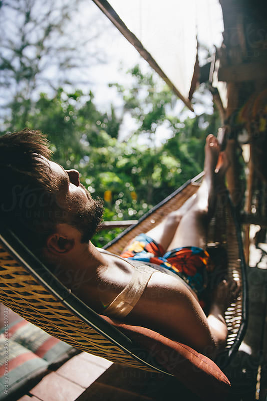 Man sleeping in hammock by Andrey Pavlov for Stocksy United
