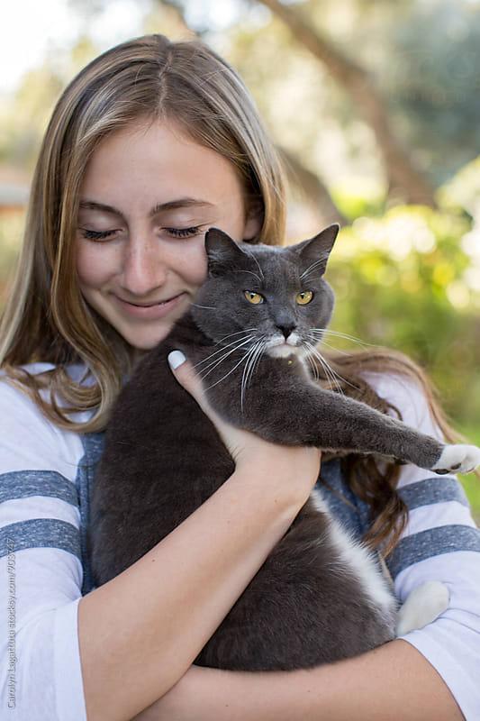 Teenage girl hugging a grey cat by Carolyn Lagattuta for Stocksy United