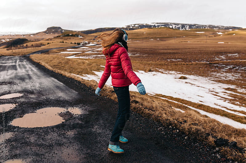 Anonymous woman in a windy winter road by Lucas Ottone for Stocksy United