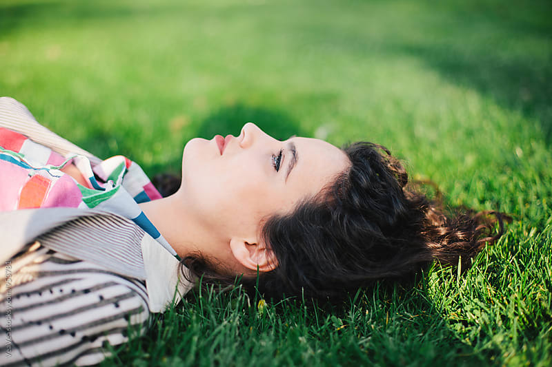 Beautiful woman lying on grass in a park by Marija Mandic for Stocksy United