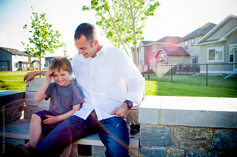 father and son sitting on a bench by Tomas Kraus for Stocksy United