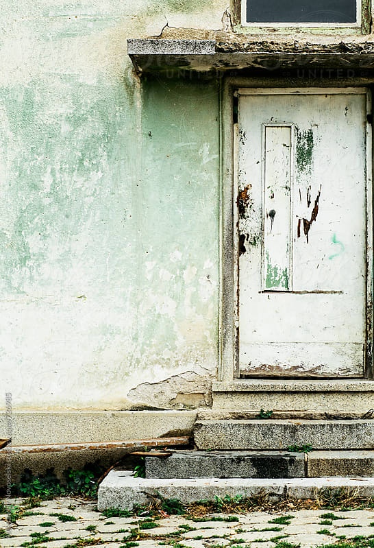 Building entrance with white door and old green wall by Aleksandar Novoselski for Stocksy United