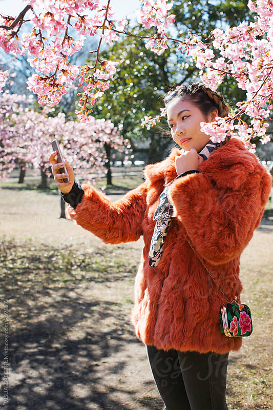 Pretty Young Japanese Woman Posing and Taking Selfie in Front of Blossoming Sakura Tree by Julien L. Balmer for Stocksy United