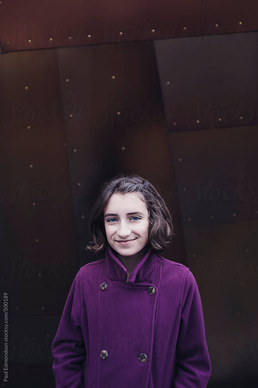 Portrait of happy eleven year old girl, in front of modern building by Paul Edmondson for Stocksy United