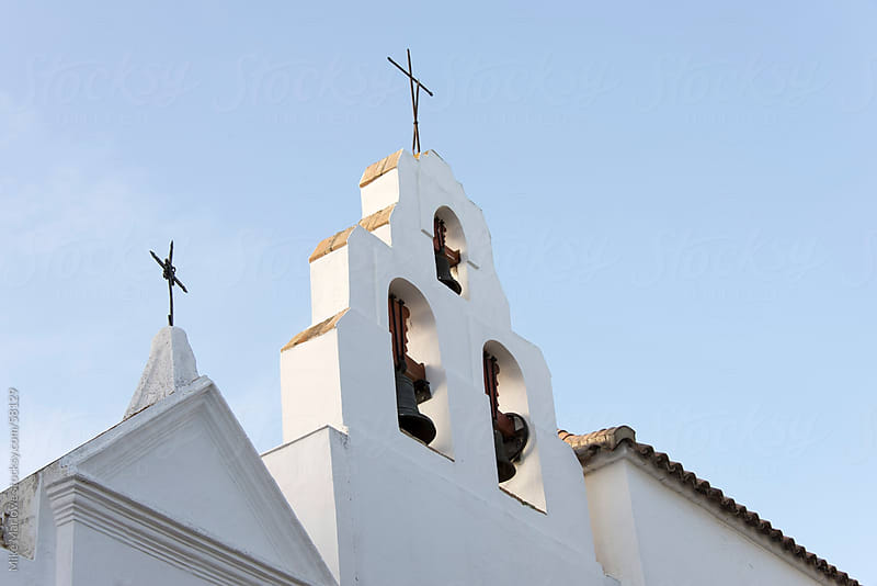 The cross and bell tower of Catholic church in Spain. by Mike Marlowe for Stocksy United