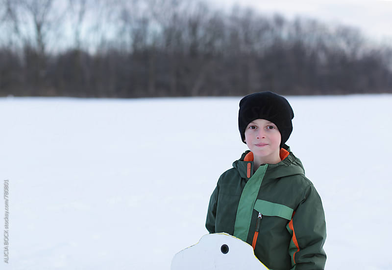 A Boy Walking Through Snow To Go Sledding by ALICIA BOCK for Stocksy United