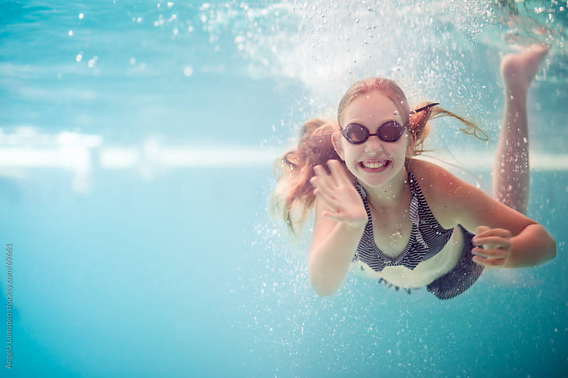 Underwater image of a girl in a swimming pool by Angela Lumsden for Stocksy United