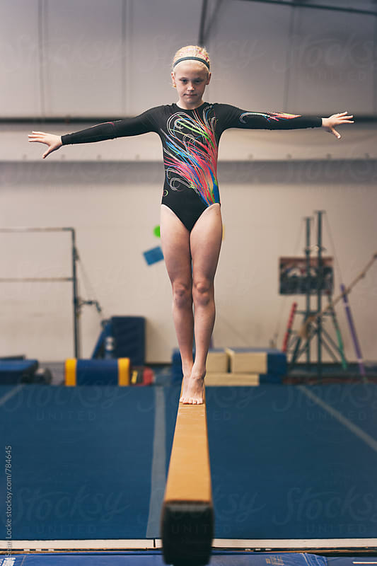 Gymnastics: Young Girl Practicing Routine On Balance Beam by Sean Locke for Stocksy United
