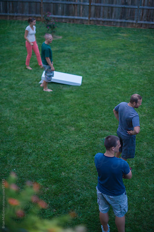 Mid 20s adults playing backyard recreational bean bag toss game by Brian McEntire for Stocksy United