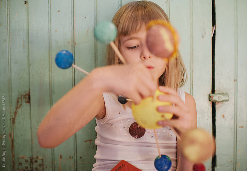 Young girl playing with her homemade solar system craft for science by Kristin Rogers Photography for Stocksy United