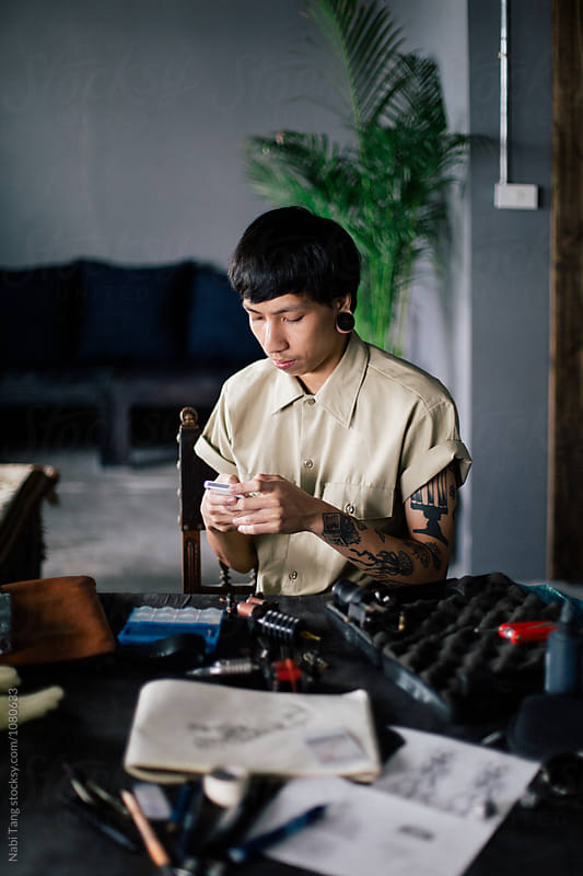 Tattoo artist in chilling in the studio by Nabi Tang for Stocksy United